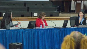 Bd mbr Gloria Torres (L) asks acting supt Rebecca Kaye (R) questions about plans as bd chair Paula Lewis (c)
