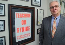 AFT Ed Allen in front of strike poster solidarity