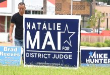 Man pulling up campaign signs 2018-6-12